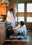 Picture of a happy couple in their white bath robes cooking in the mornig. She is sitting on the counter top holding a glass of juice, and he is uising oven mits to take a pan out of the oven.